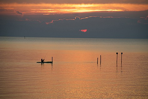 Picture perfect sunset and kayaker in silhouette on AIE