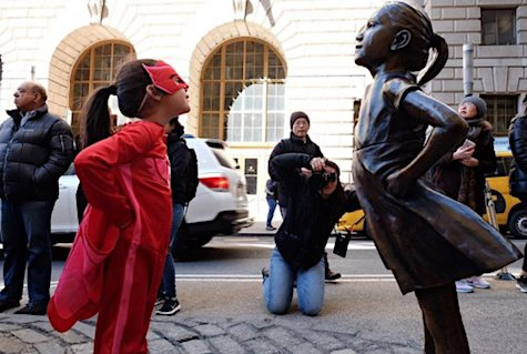 "Abrianna Tabor Almonte wears her red-and-pink superhero outfit to go see the ""Fearless Girl"" statue on Wall Street. (Credit: Amanda Marmor via CNN)_AIE"